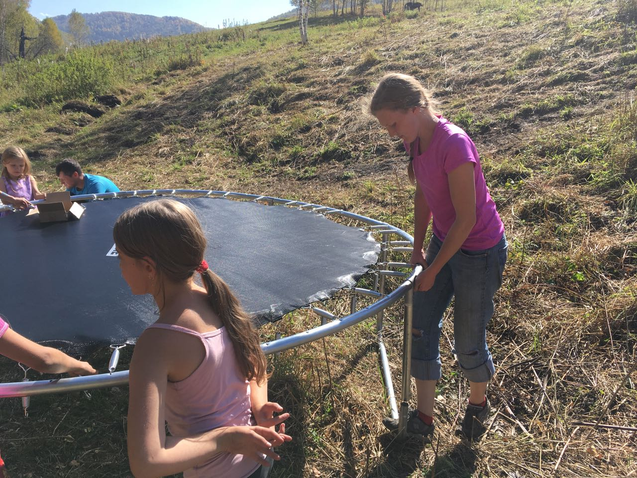 girls setting up trampoline